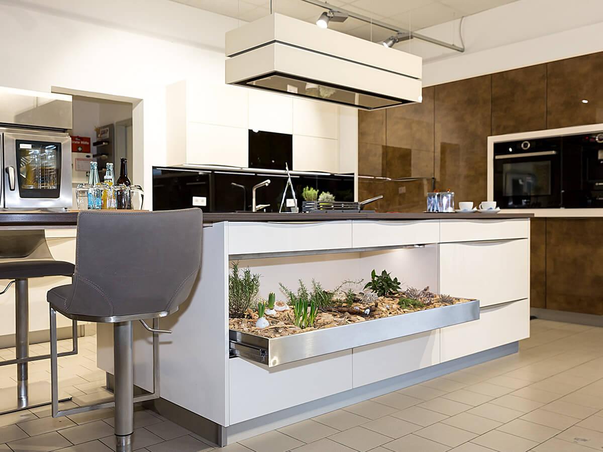 Weisser Küchenstudio Showroom Kochinsel mit integrierter Begrünung