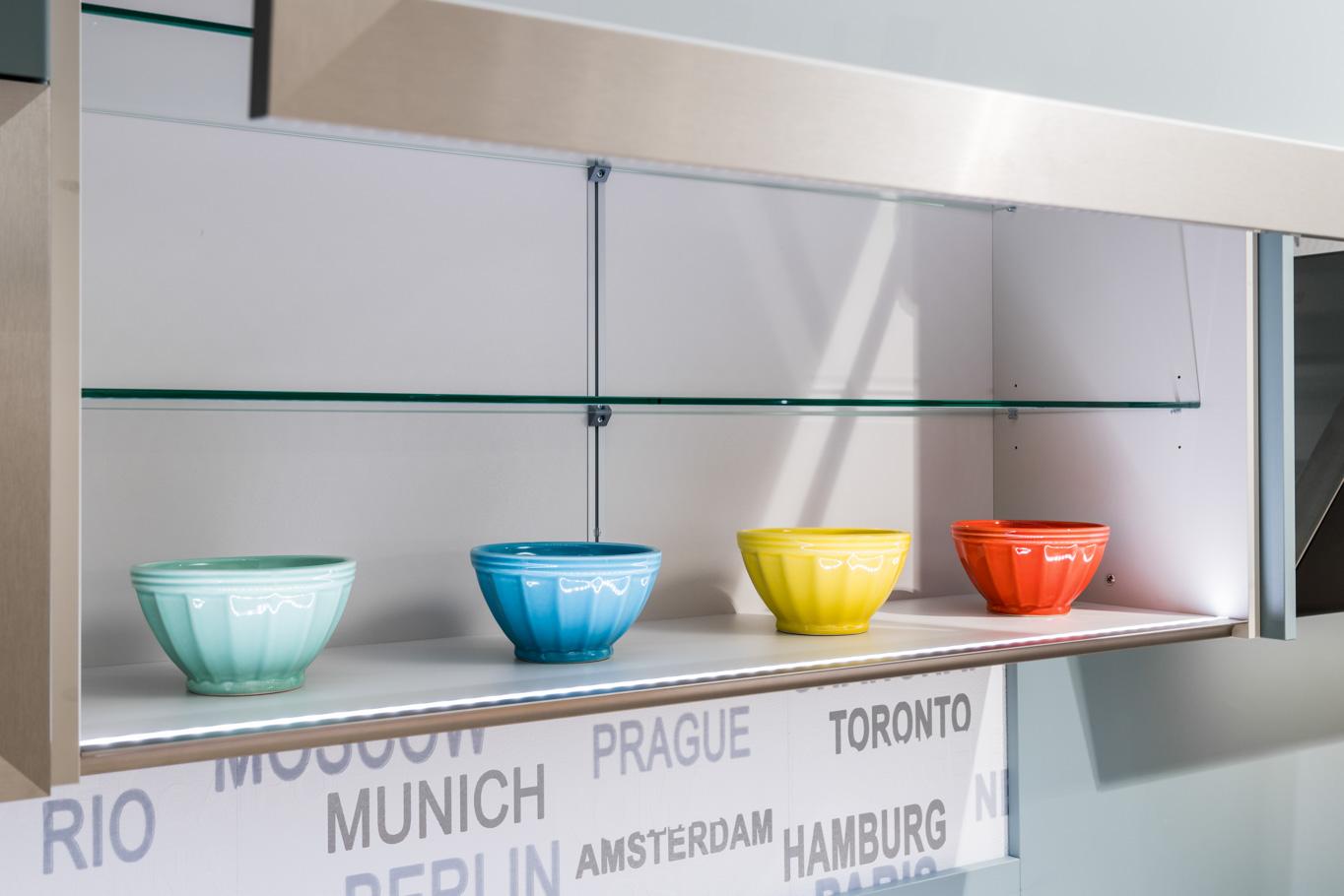 Weisser Küchenstudio Showroom bunte Schalen in einem Regal